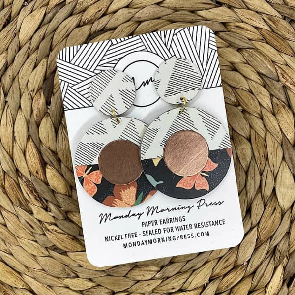 circular copper peach, black, and white statement earrings on display card