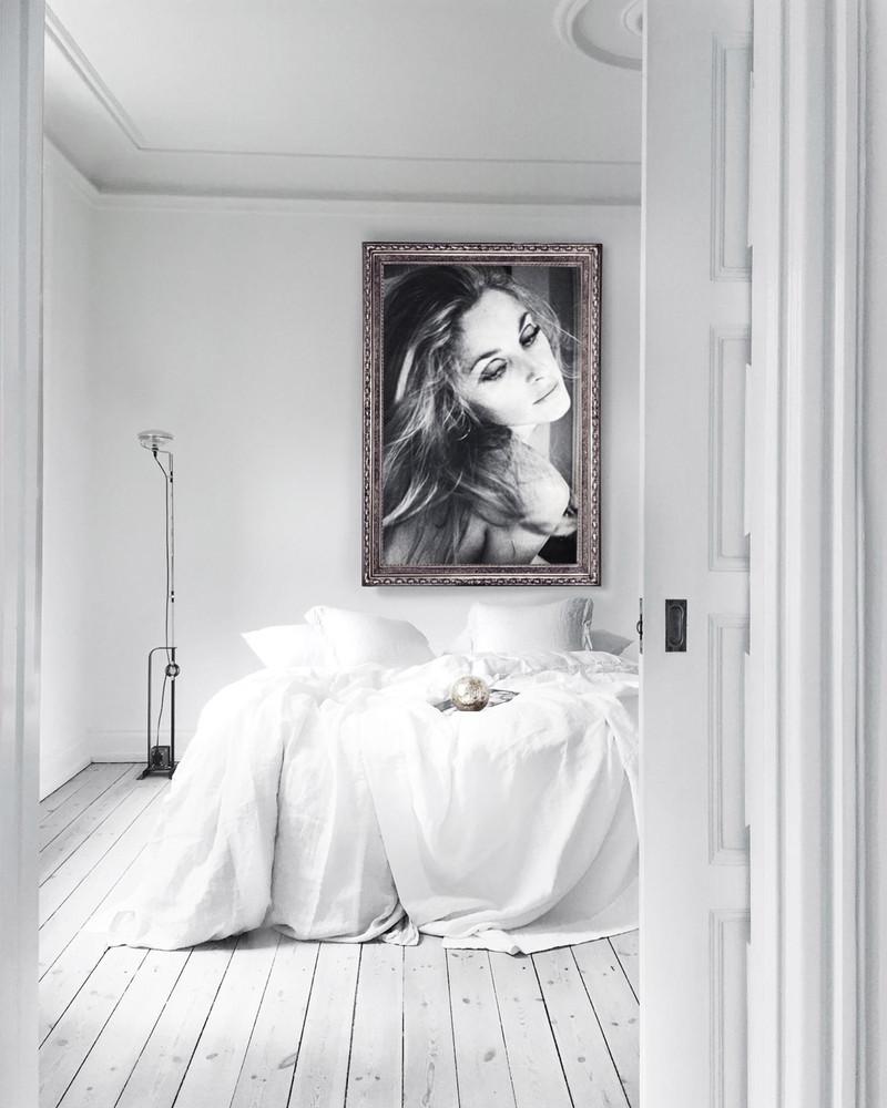 Dormitorio de estilo minimalista con cama blanca sin cabecero y un retrato grande.