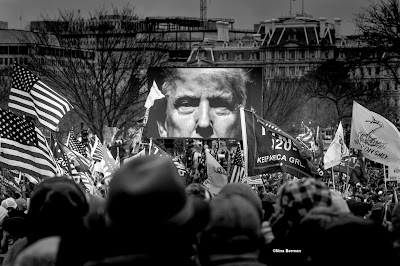 Black and white photo of President Trump on giant screen at a rally outside the White House.