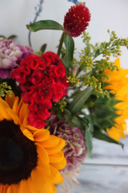 Huckleberry, Salvia, Solidago, Charmelia, Gomphrena, Celosia, Dahlias, Carnations, and Sunflowers.