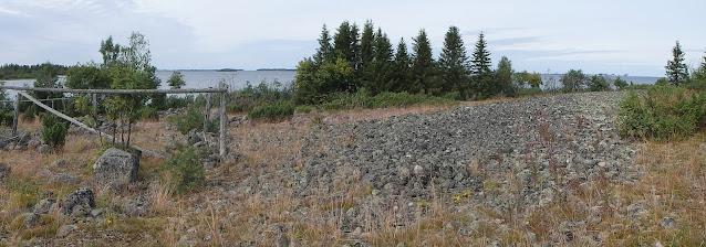 Maalta merelle päin otettu kuva. Rannalla on siellä täällä puita ja maa koostuu suurelta osin päänkokoisista pyöreistä kivistä. Kuvan vasemmassa laidassa on puinen telinerakennelma, jota on ennen muinoin käytetty kalaverkkojen kuivaamiseeN.