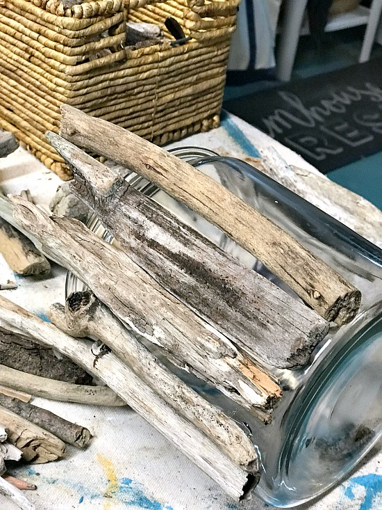 Driftwood lined up on the outside of a glass vase