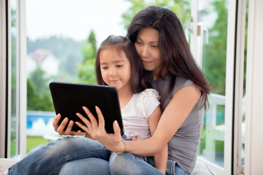 Woman and girl using tablet computer.