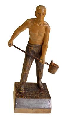 Puusta veistetty patsas esittää paidatonta, lyhythiuksista miestä, joka pitelee käsissään pitkävartista raudanvaluastiaa.