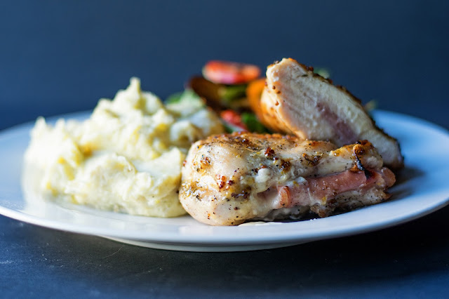 The Grilled Chicken Cordon Bleu, on a plate with a salad and mashed potatoes.