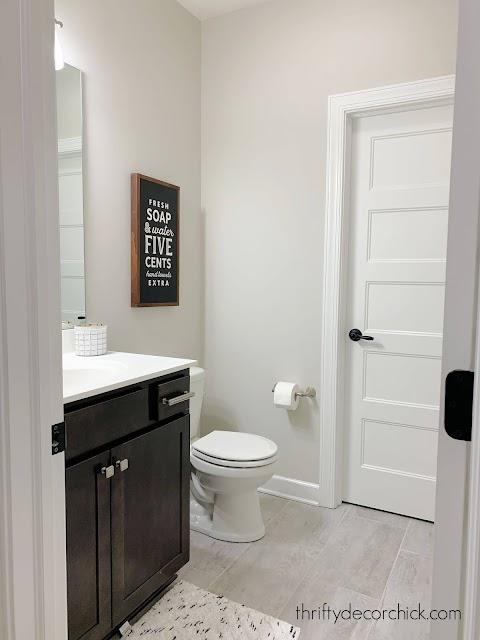 bathroom with tile dark vanity
