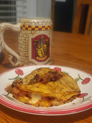 Gryffindor beer stein behind a red and white plate painted with cherries. on top of the plate is a tortilla sandwich with cheese spilling out and a dollop of salsa on top