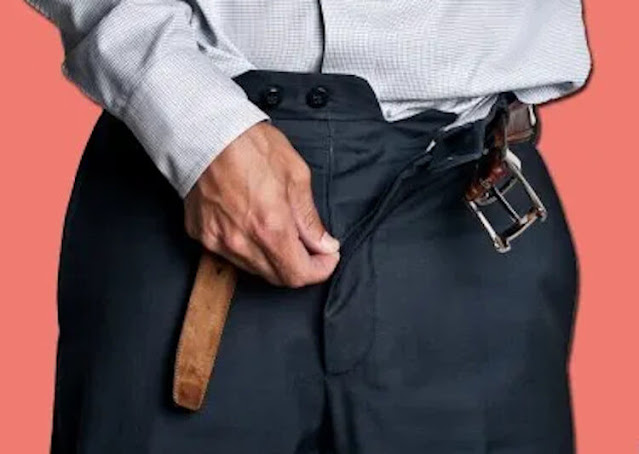 Men unzips trousers photo in a tailor to measure his size