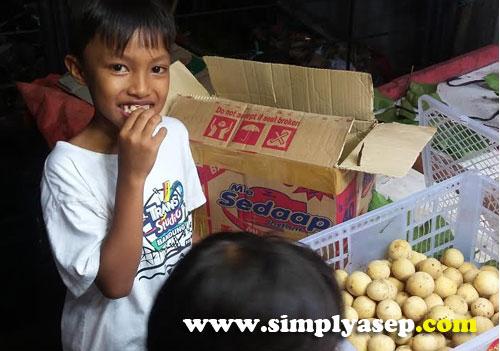 "TESTER :  Anak saya , Abbie 8 thn, sedang mencicipi buah Langsat. ""Yang ini boleh dicoba ya"" kata penjualnya.  Oalaa ada ""tester"" nya juga ya. Foto Asep Haryono"