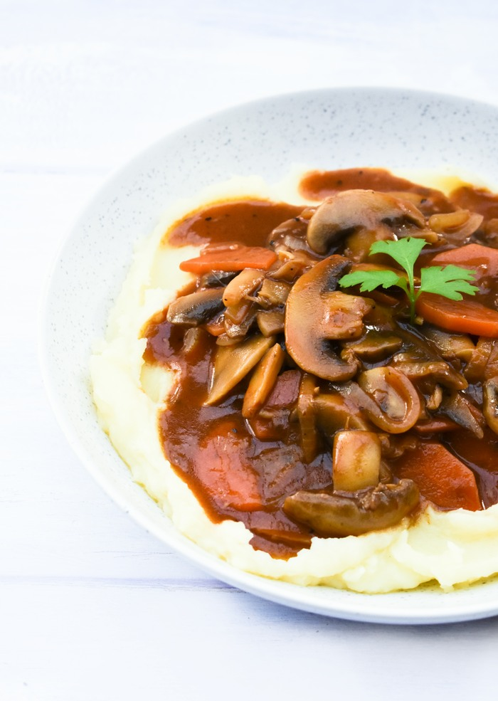A close up of mushroom stew with it's glistening, rich gravy