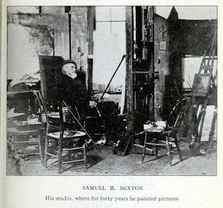 Black and white photo of old white man sitting, surrounded by easels and painting supplies.