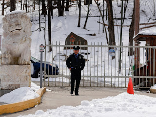A security guard walks along the drive of the main gate entry to the Falun Gong Dragon Springs compound, Friday, March 8, 2019, Julie Jacobson / AP
