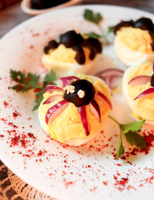 close up of spider deviled egg on a plate.