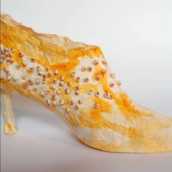 yellow and white tissue paper shoe sculpture decorated with small white beads