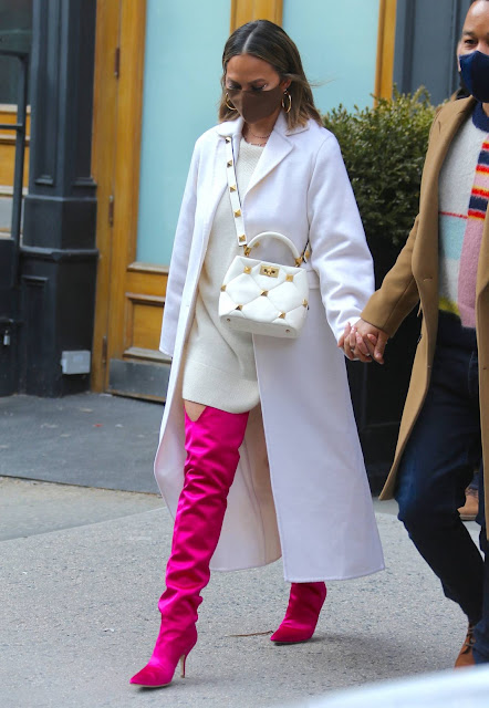 Chrissy Teigen – In thigh-high pink boots and a white dress out in New York