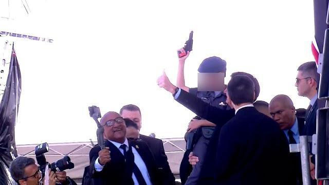 Bolsonaro posa com criança no colo com arma de brinquedo