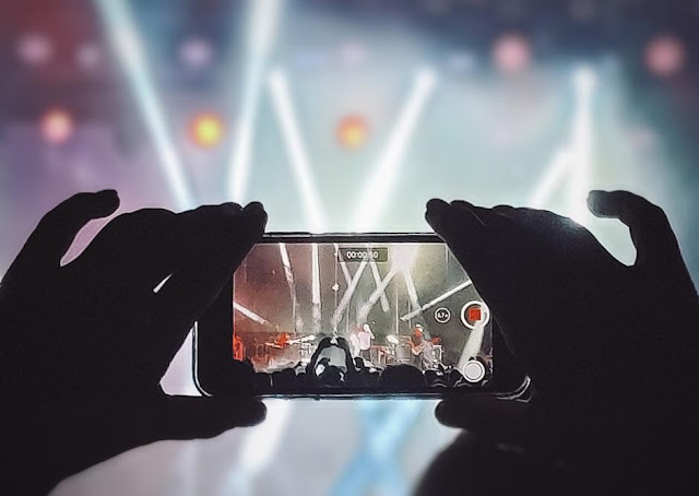 Person at a music event recording a video on their phone