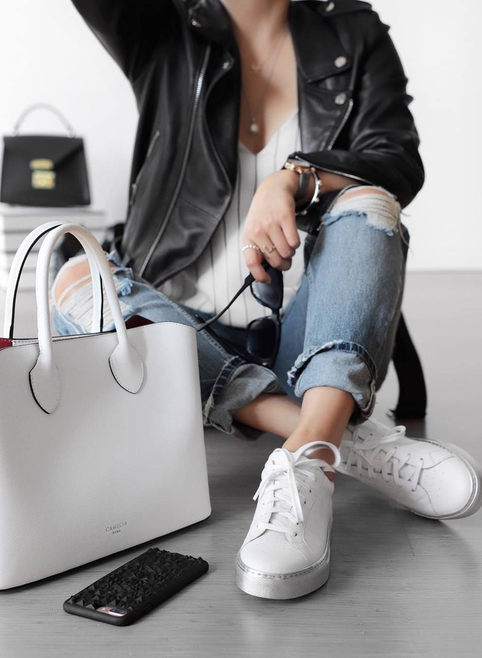street style inspiration / white bag + rips + sneakers + striped top + black leather jacket