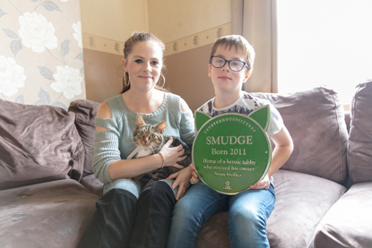 Ethan Fenton, his mum and cat Smudge with green pet plaque