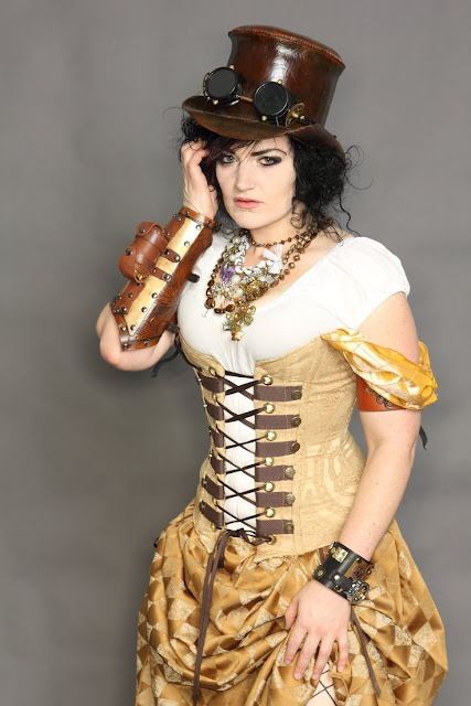 steampunk woman dressed in skirt corset gauntlet bracers and goggles