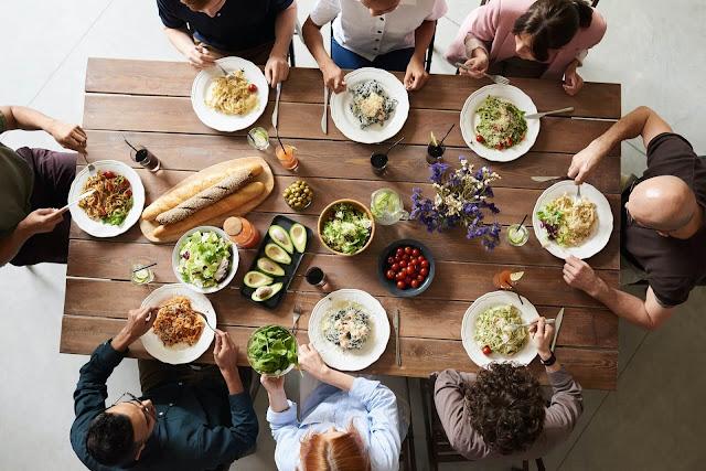 Imagen desde arriba de una mesa de comedor con ocho comensales
