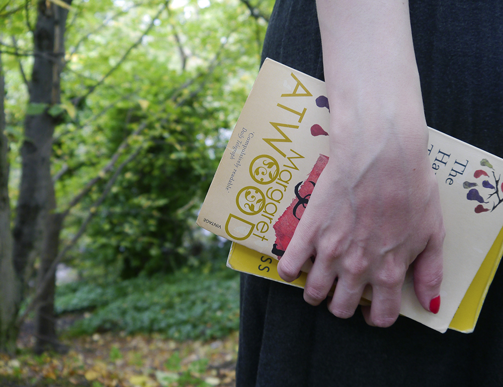 Hand holding copies of Margaret Atwood novels in the woods
