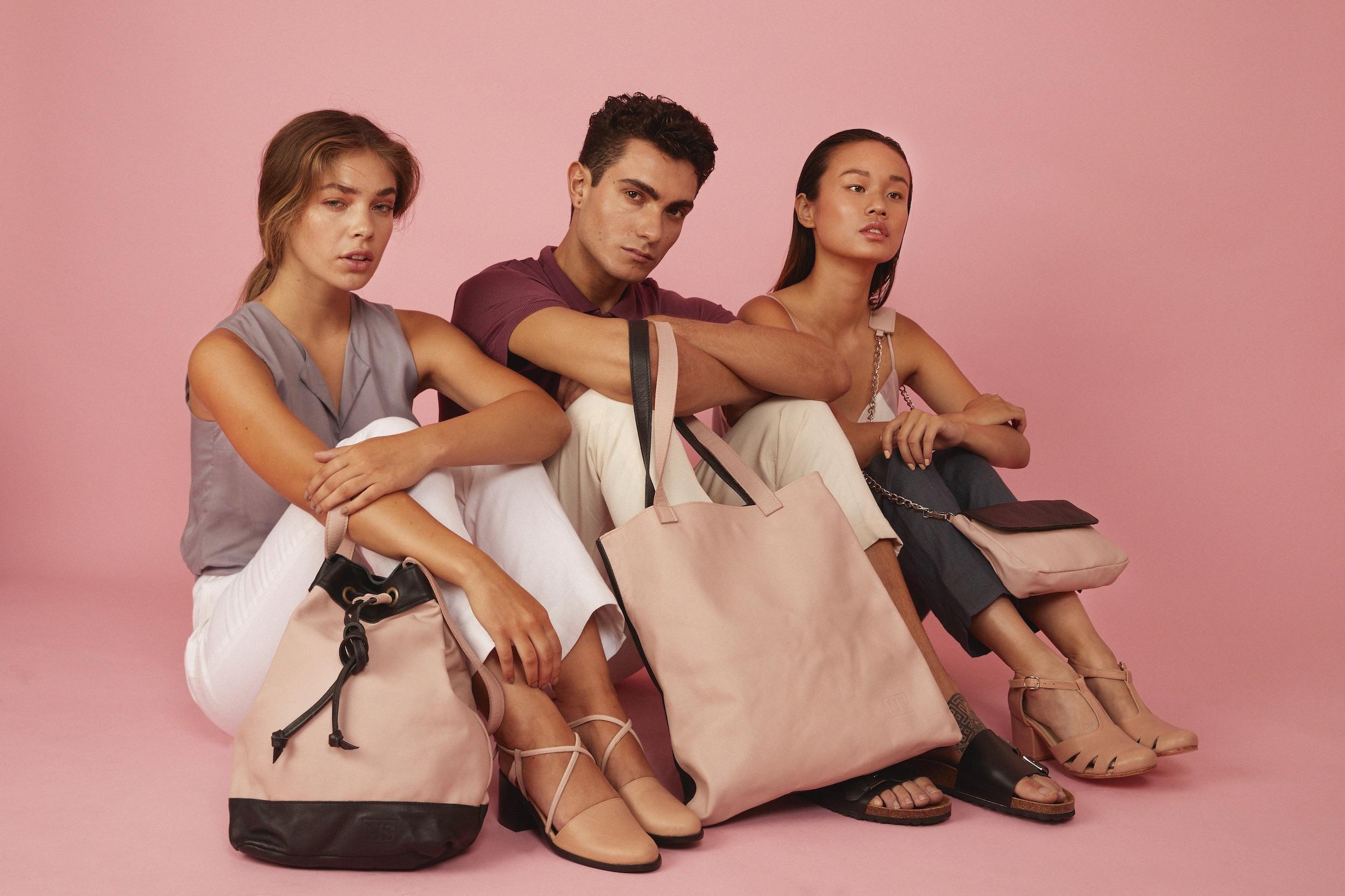 En la foto tres modelos muestran una mochila y dos carteras en tonos rosado y negro