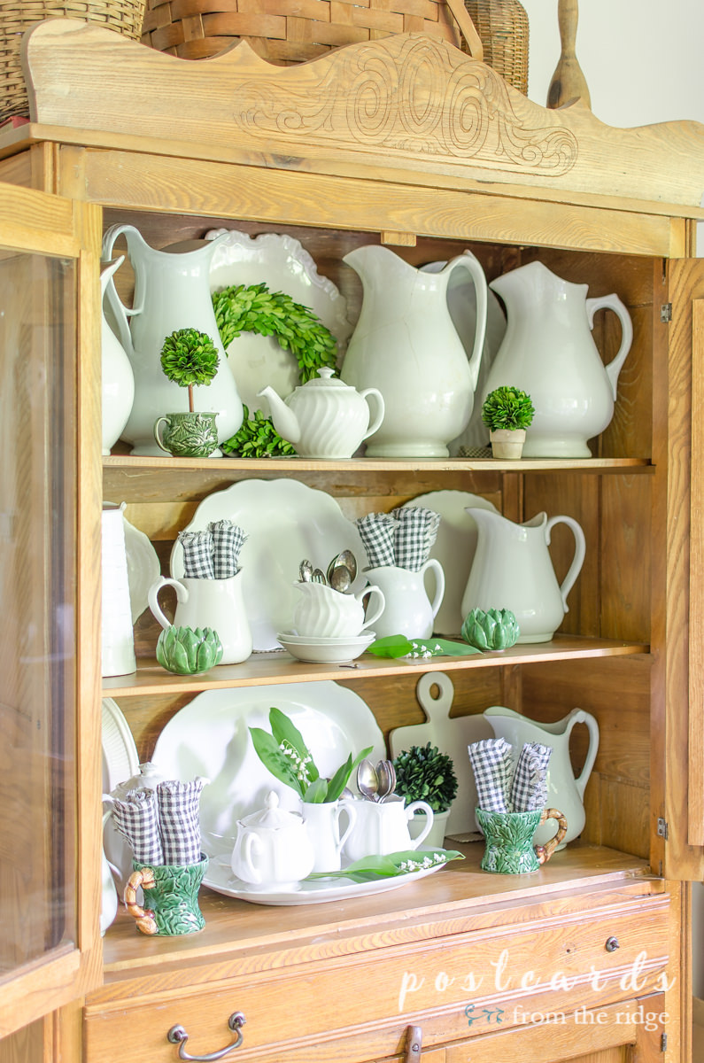 white ironstone with green and black and white accents in antique oak hutch