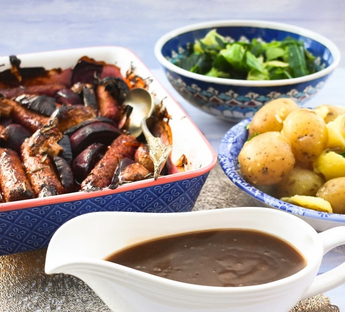 sticky sausage bake, bowl of potatoes, bowl if cabbage & a jug of gravy
