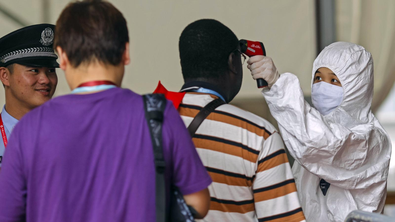 People have their temperature taken at the entrance of the Canton Fair in Guangzhou during the Ebola crisis in 2014.