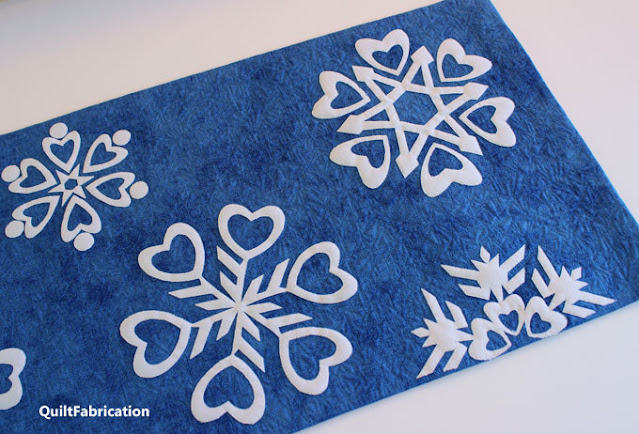closeup of four heart themed snowflakes on a table runner by QuiltFabrication