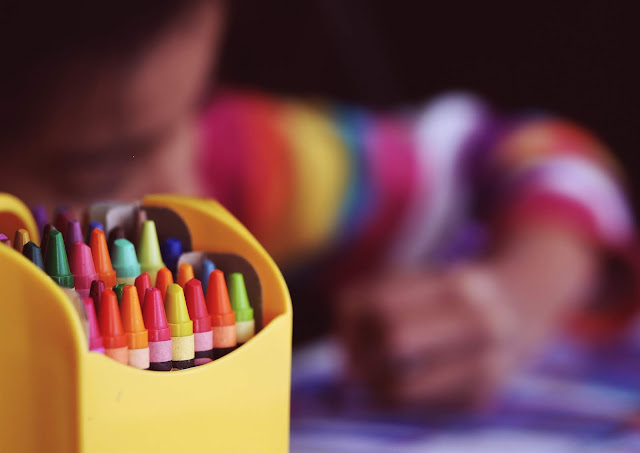 Close up of crayons with a child drawing the background