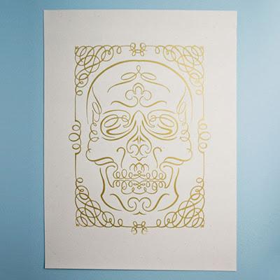 Tarjeta impresa en tinta directa dorada con ornamentos formando una calavera.