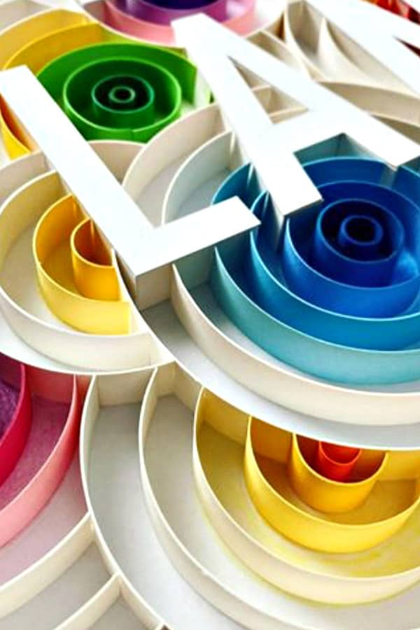on-edge colorful circular paper art with paper cut block letters