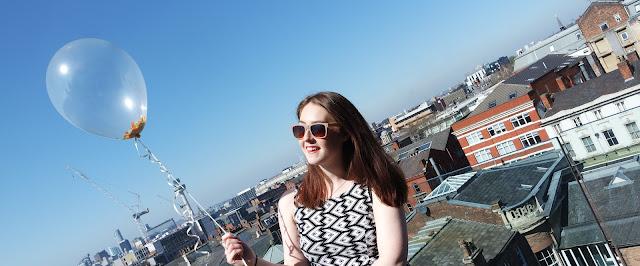 me holding a balloon on a sunny balcony