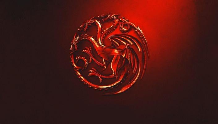 Imagem: fundo em vermelho-escuro com o símbolo metálico e vermelho da Casa Targaryen, um dragão de três cabeças.