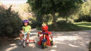 Elmo is riding his tricycle through the park. Elmo sings Elmo's Riding. Sesame Street The Best of Elmo 2