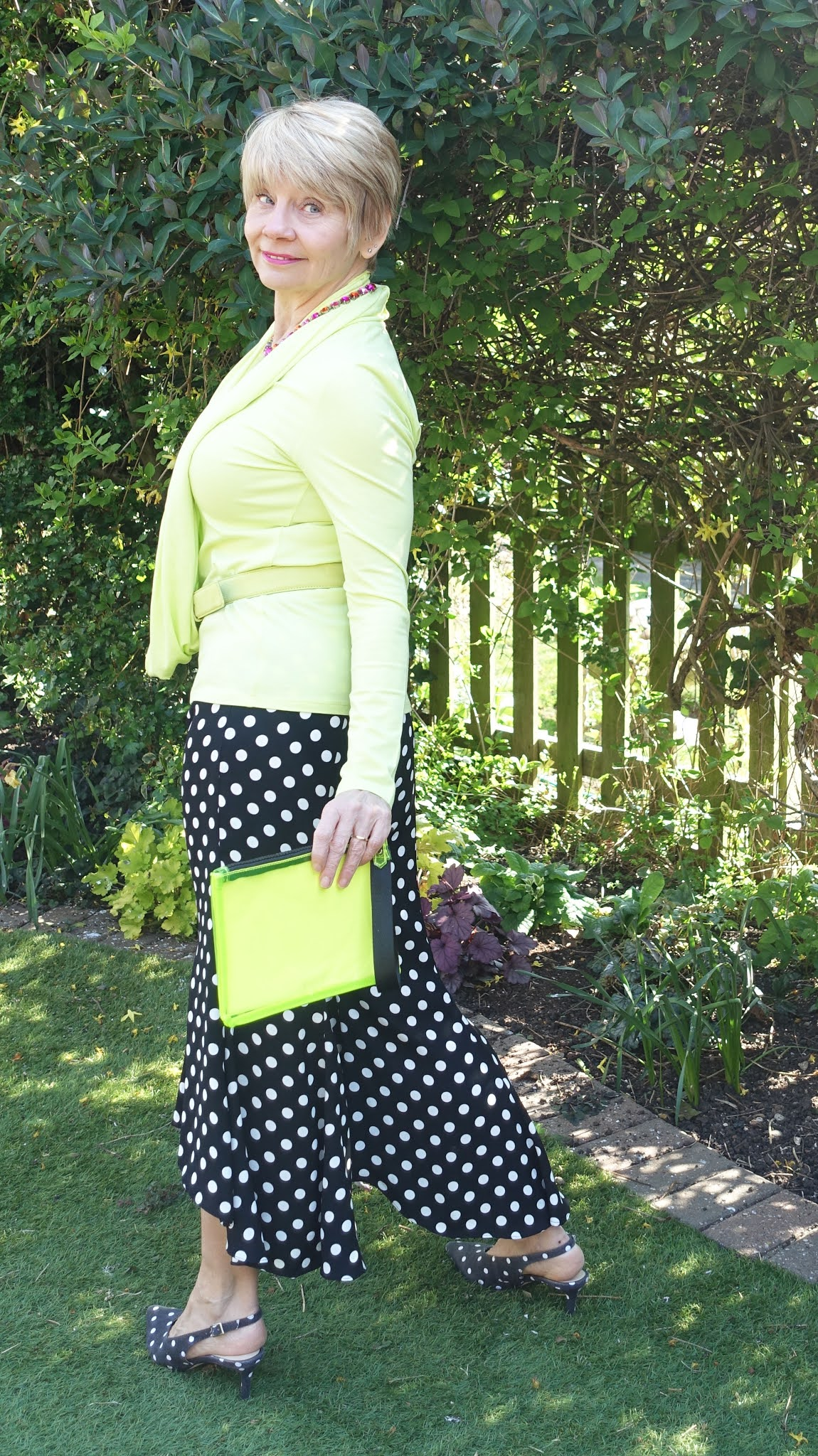 Back view of Is This Mutton blogger Gail Hanlon in acid yellow top and scarf with black and white polka dot trousers