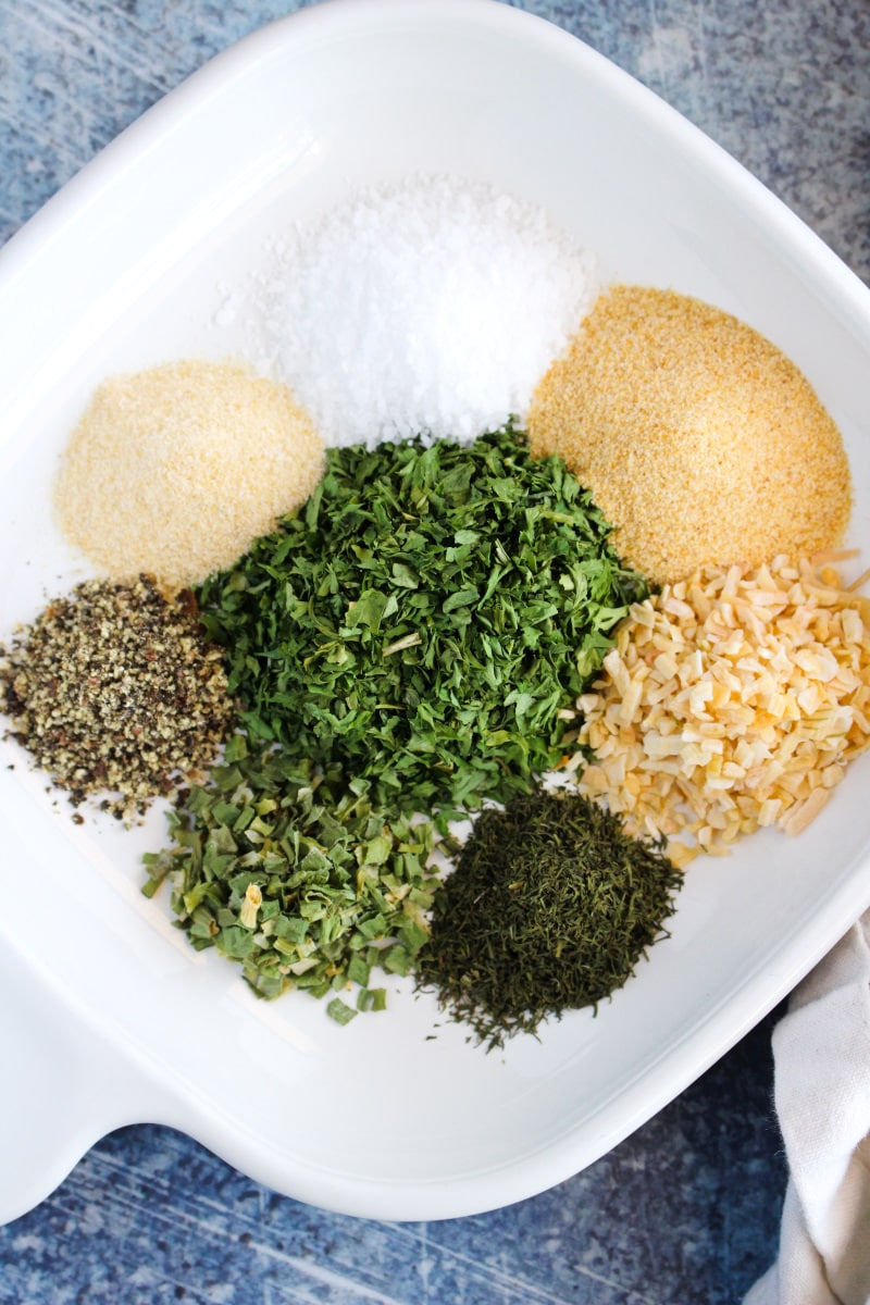 Top view of ranch mix ingredients unmixed on a white plate placed on a blue background.