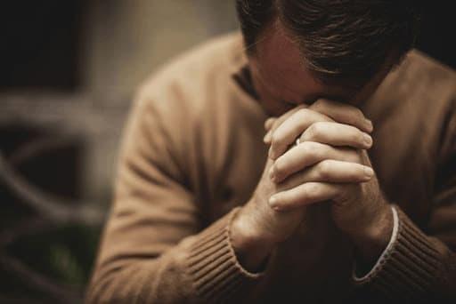 A imagem mostra um homem de mãos fechadas orando.