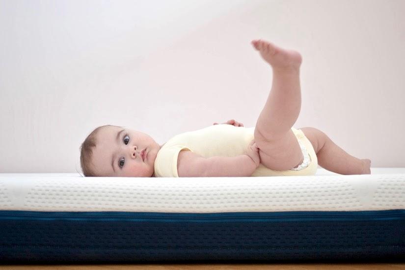Bebé lactante de más de 6 meses tumbado y moviendo las piernas