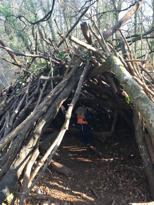 den made from sticks with toddler inside