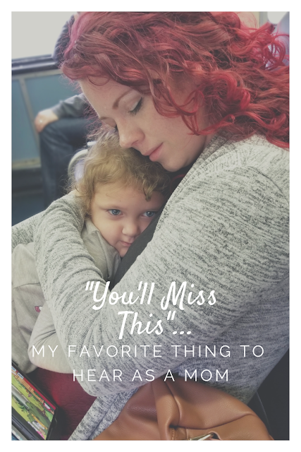 Red headed mother in a grey sweater hugging her curly blonde daughter