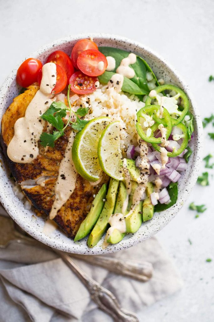 Paleo Fish Taco Bowls - These Paleo Fish Taco Bowls are such a well balanced meal! They are filled with delicious pan fried barramundi, aka The Sustainable Seabass® fillets, lots of veggies, cauliflower rice, and topped off with a creamy cashew chipotle sauce! Sign me up for this quick and easy, nutritious, and delicious meal please!