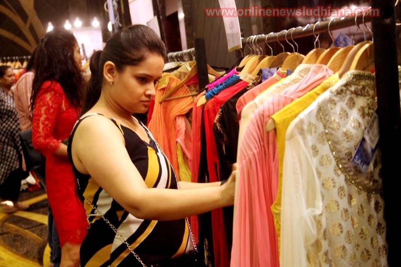 प्रदर्शनी के दौरान डिज़ाइनर कपड़ो को देखते एक महिला