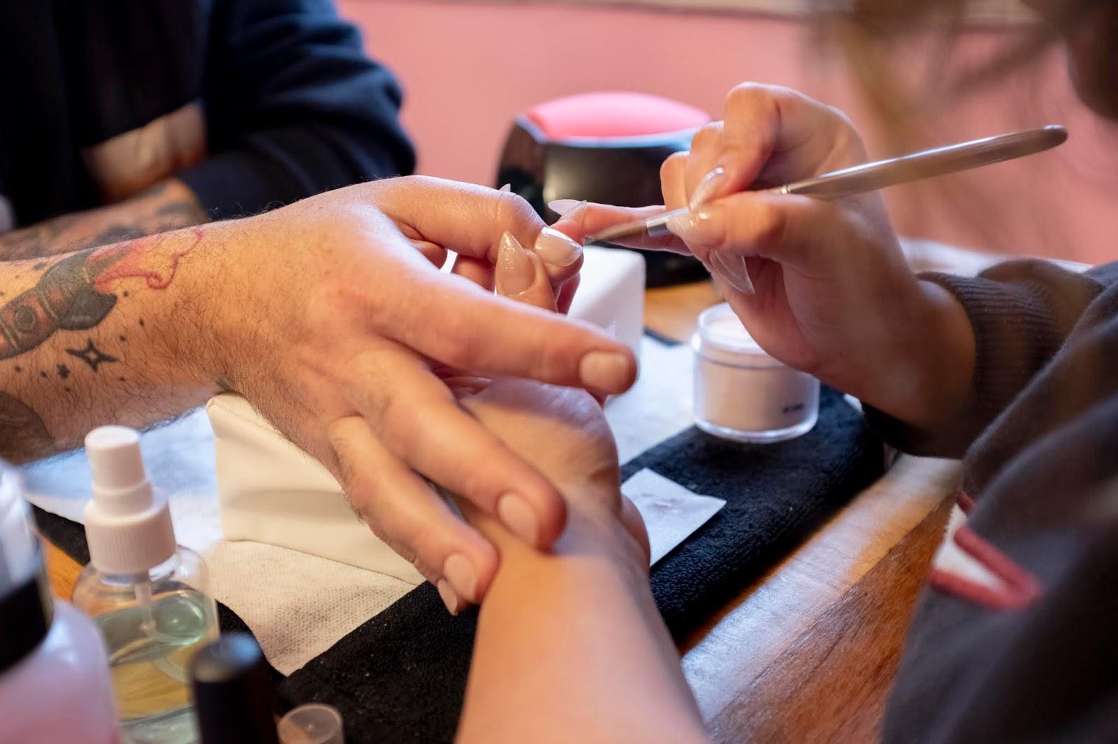 Sr. González en proceso de hacerse uñas acrílicas en salón La Casanova