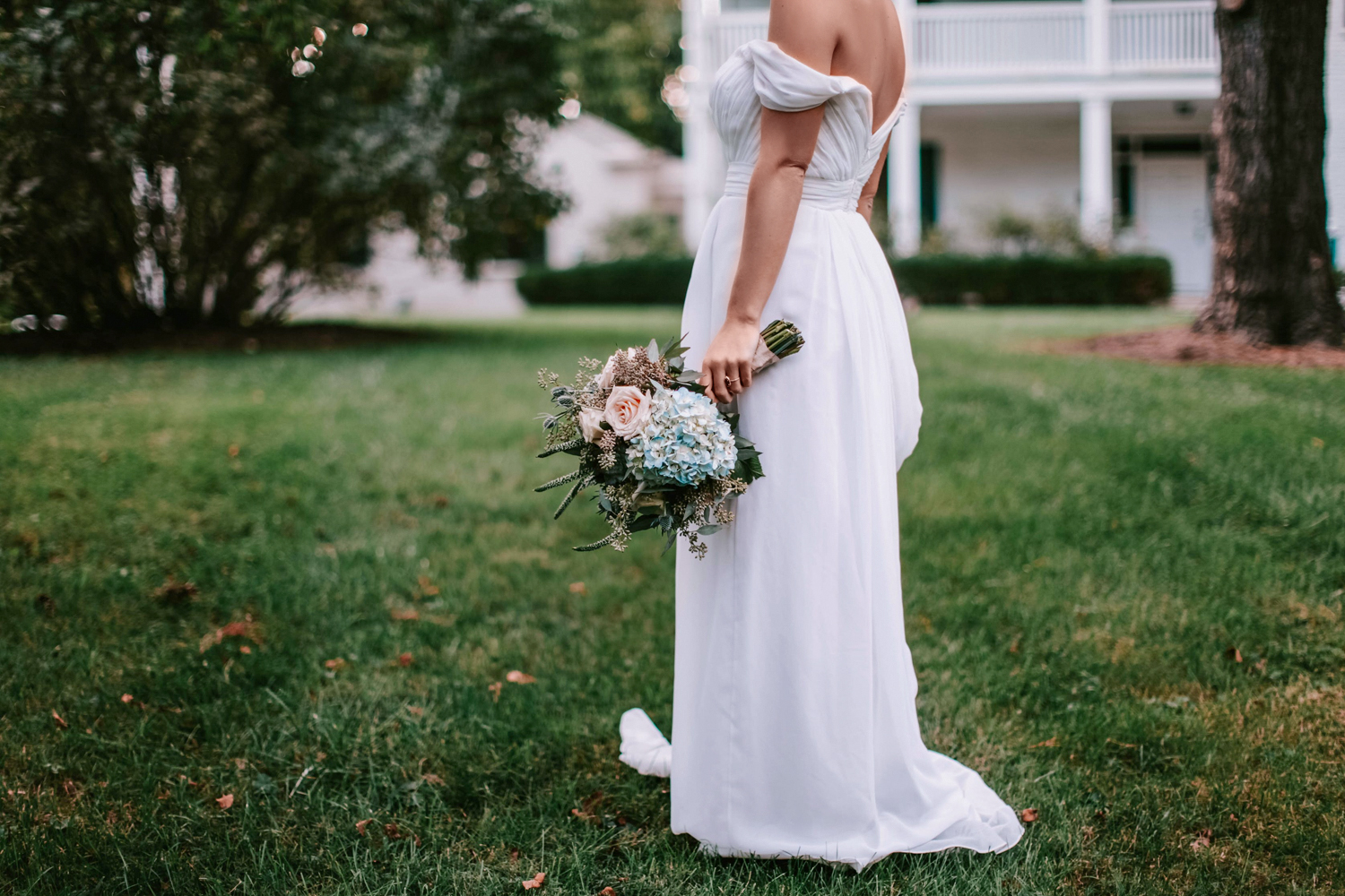 bride in a long dress holding bouquete and posing on the grass