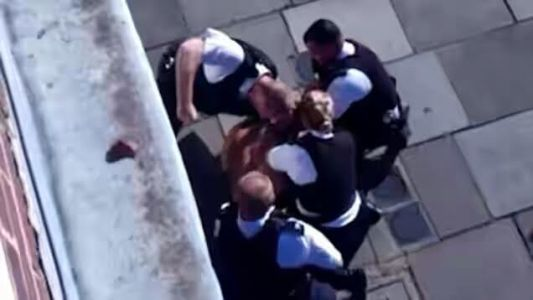 Footage filmed in UK shows policeman punching suspect multiple times while 3 other officers hold him down (video)