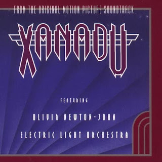 Xanadu written in pointed burgundy writing outlined in white on a purple background - just as 80s as it sounds.