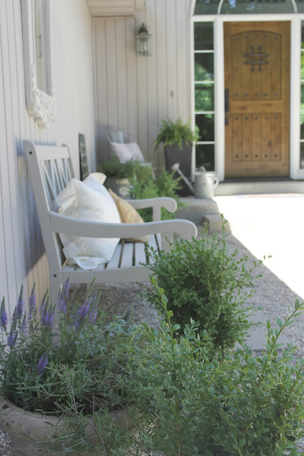 Beautiful French inspired courtyard with boxwood, lavender, and knotty alder door - Hello Lovely Studio
